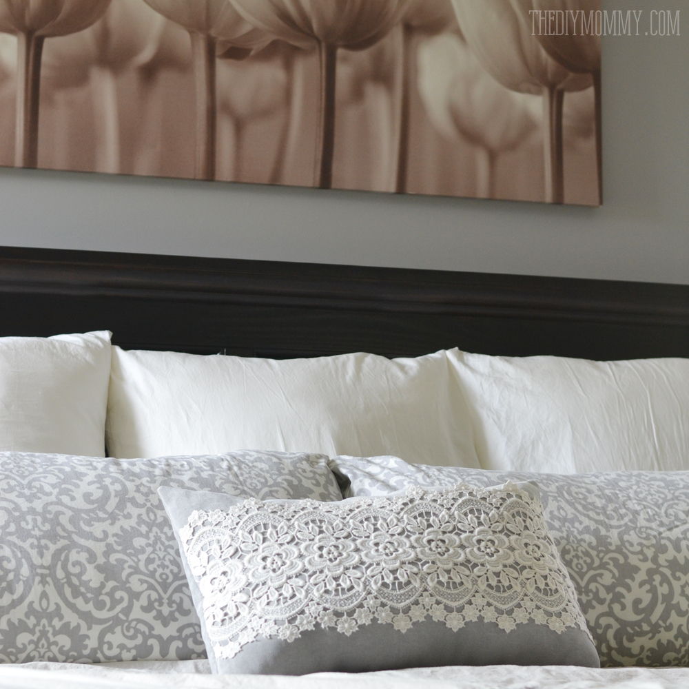 A serene grey and white master bedroom with DIY pillows.