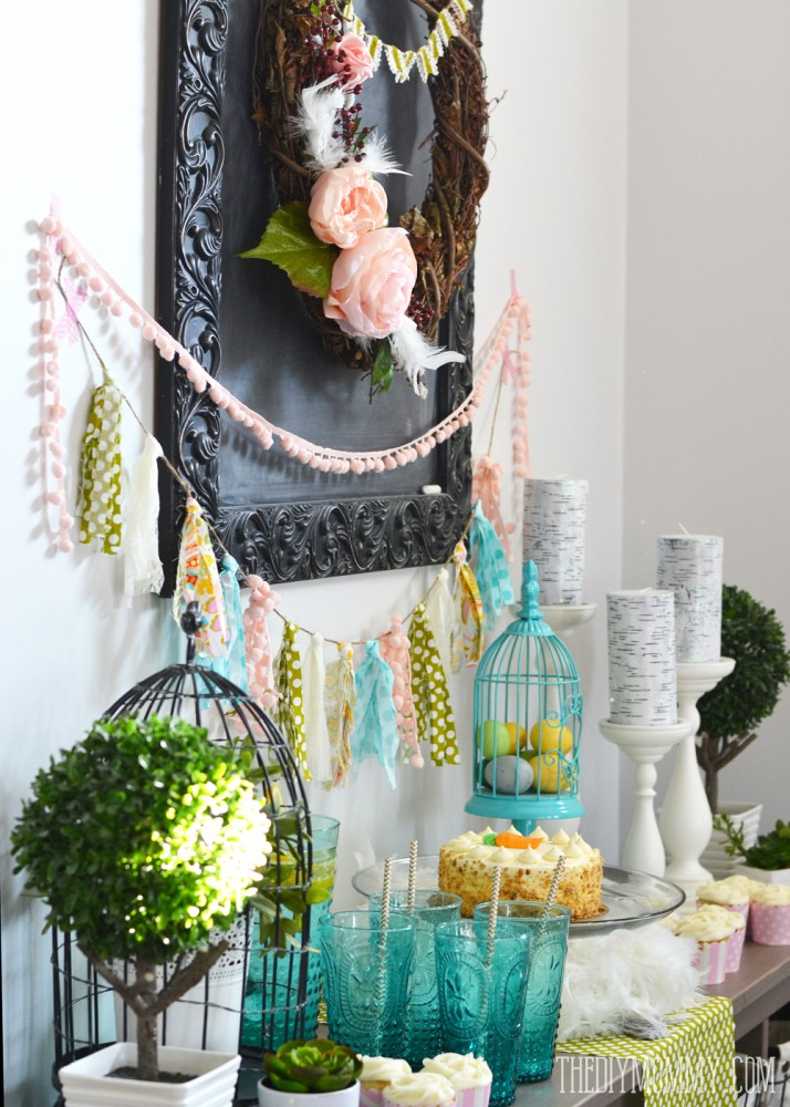 A Fresh & Happy Dessert Table Idea for Spring! A DIY wreath and DIY fabric scrap tassle banner take center stage in this fun aqua, blush pink, moss green and yellow dessert table featuring bird cages, birch candles, feathers and greenery.