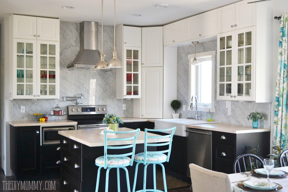 A beautiful vintage industrial kitchen featuring black and white Ikea cabinets, turquoise accents and a Carrara marble stone panel backsplash.