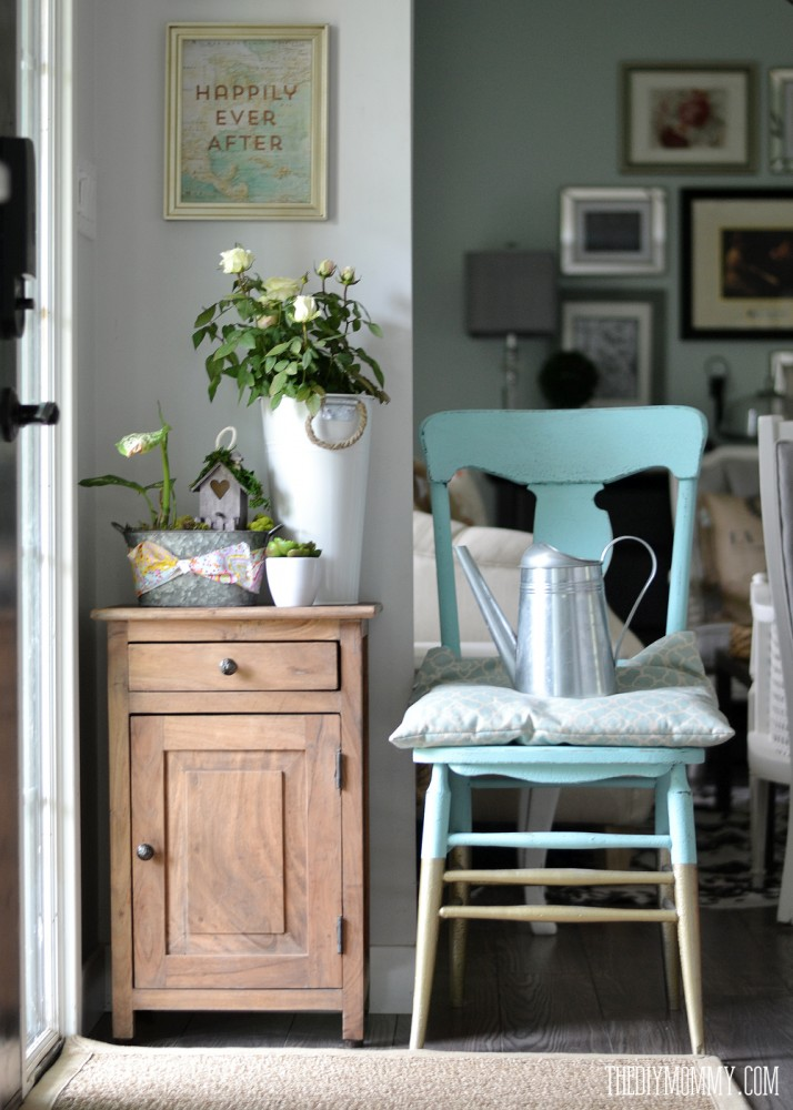 Acacia wood entry cabinet, free map artwork and a turquoise and gold dipped chair at entry