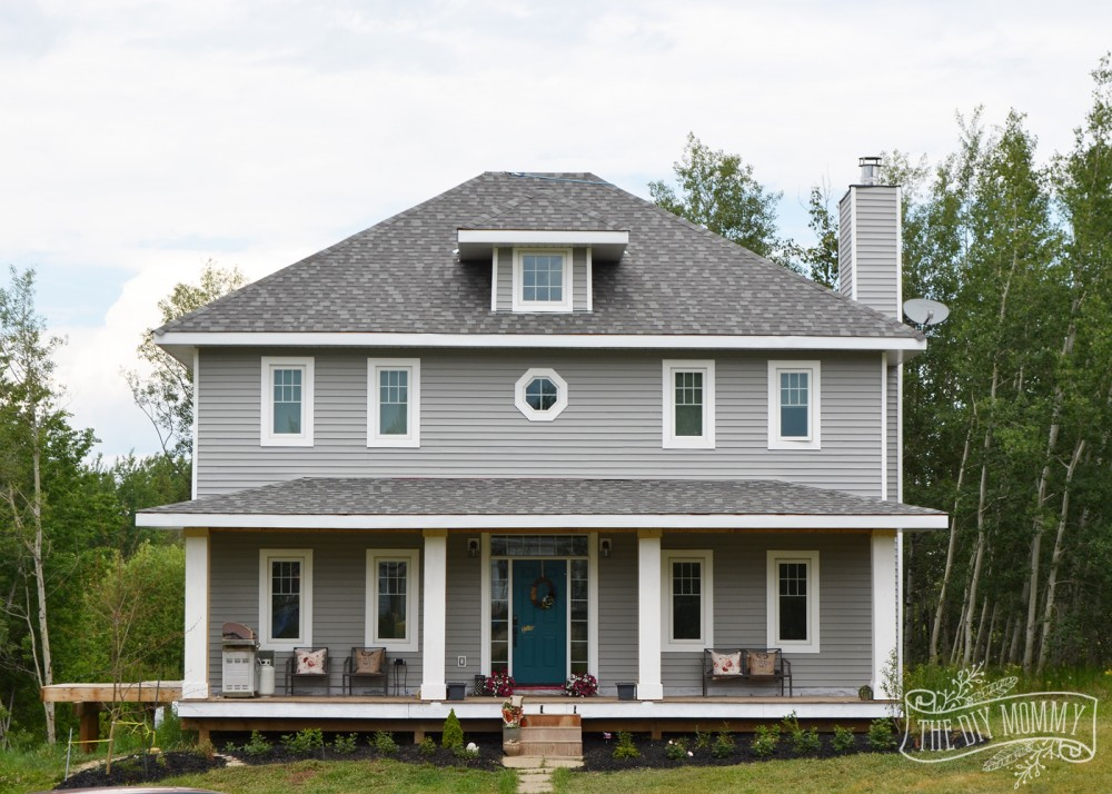 Gray foursquare new home with white trim and teal door