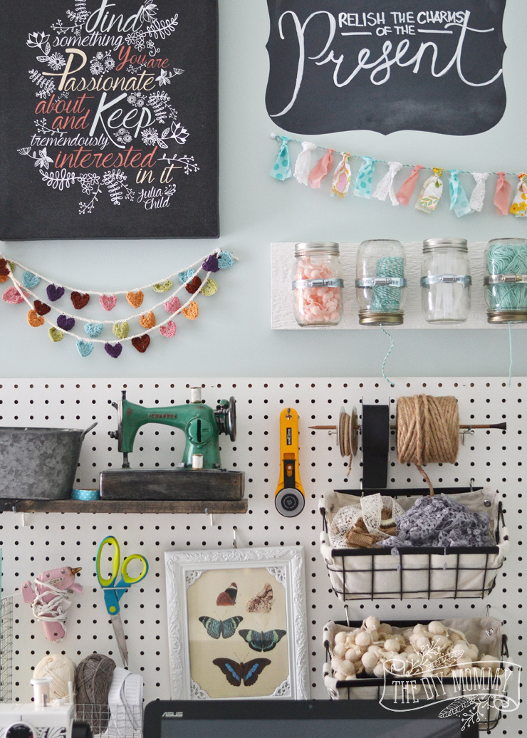 A beautiful, colorful craft room office wall with pegboard for storage, baskets, #DIY garlands, art and hanging mason jar storage.