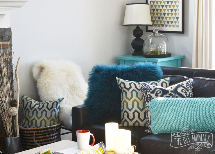A black leather sofa with teal, green and turquoise pillows