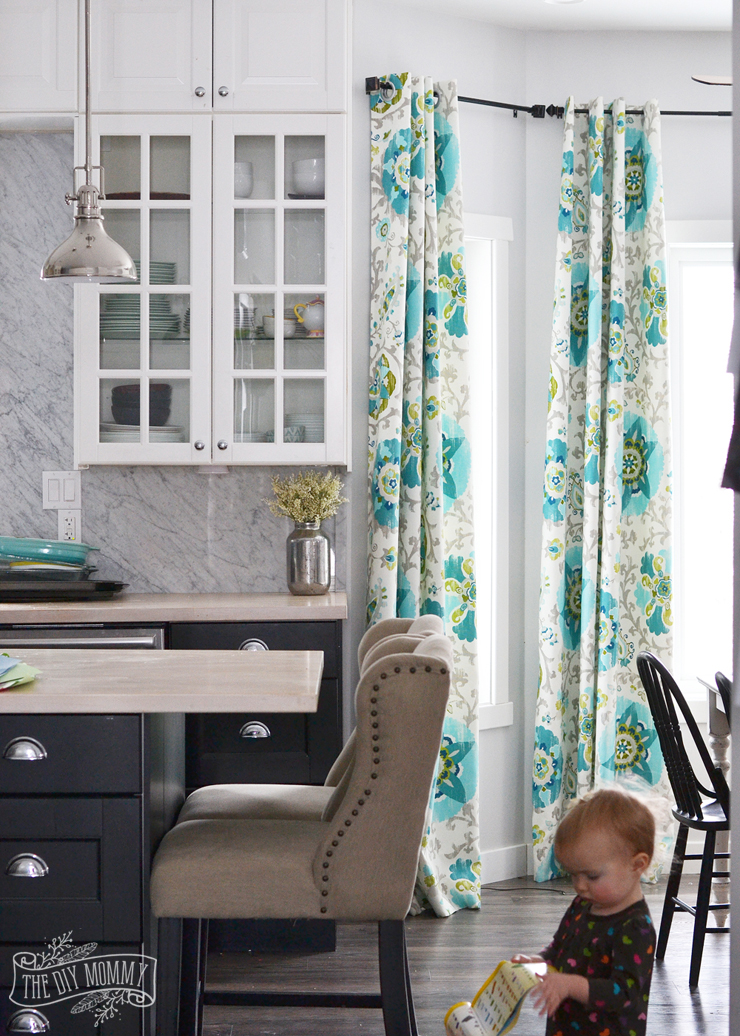 A black and white kitchen with turquoise and teal floral drapes