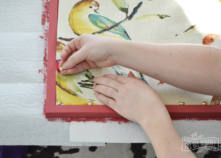 How to make a covered bulletin board with paint, fabric and brass upholstery tacks.
