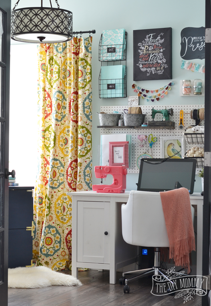 A colorful boho craft room home office with tons of great DIY decor and organization ideas.
