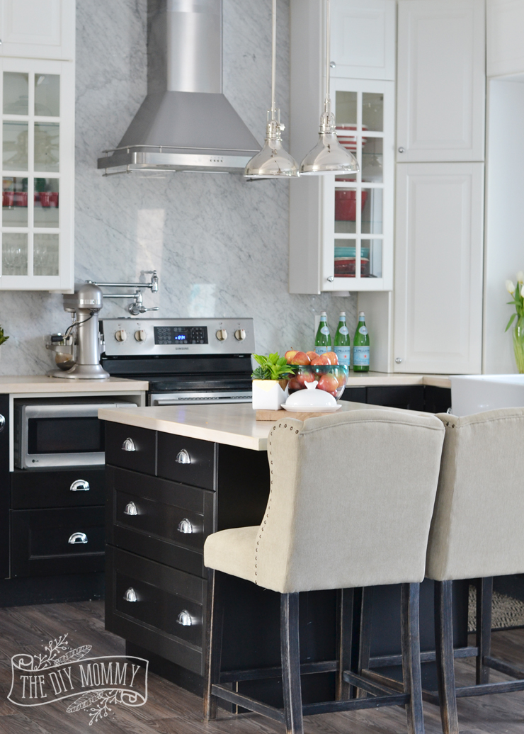 A black and white kitchen with a Carrara marble backsplash