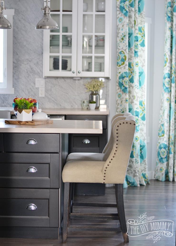 A black and white kitchen with a Carrara marble backsplash