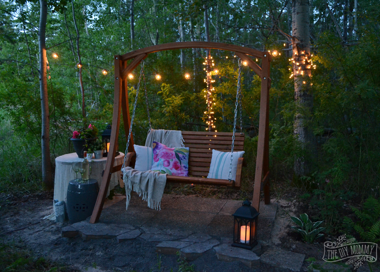 A secret garden swing retreat - the perfect little mini patio in the woods with a shade garden, a wooden swing, and a side table for drinks