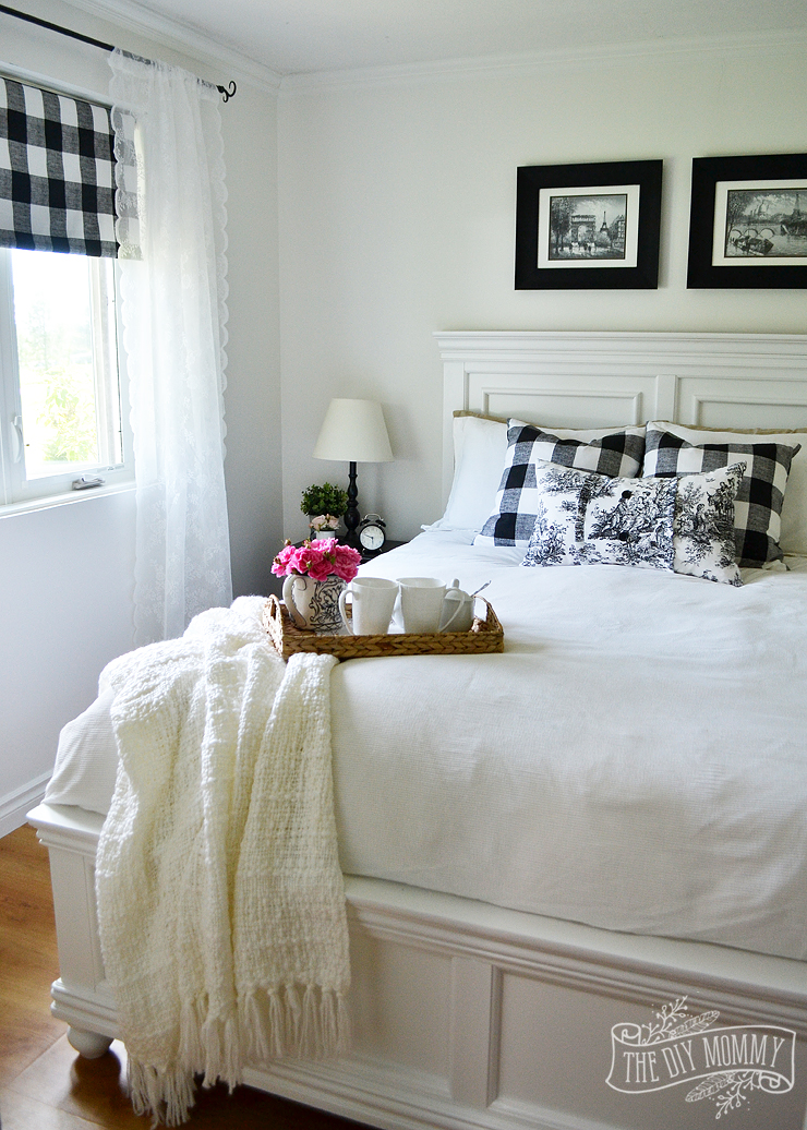 a black and white farmhouse cottage bedroom design with buffalo plaid toile