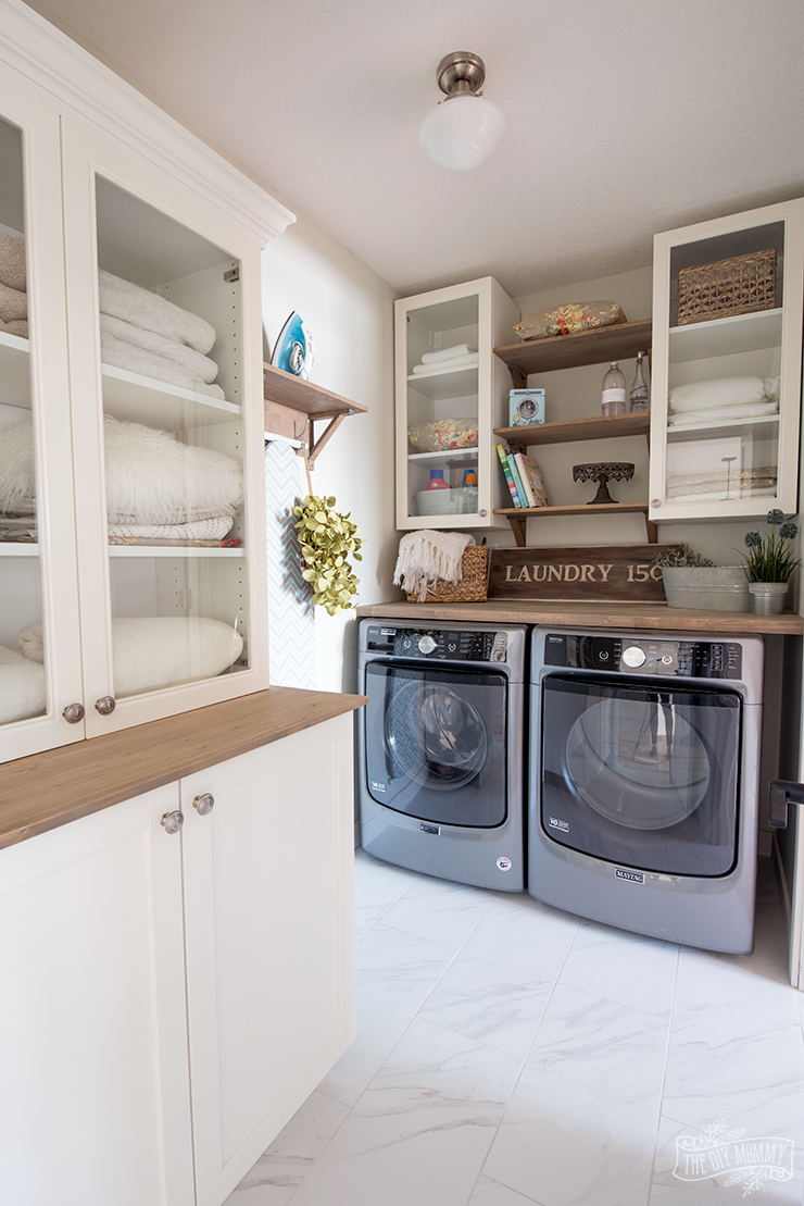 Farmhouse lake cottage laundry room design in white, green, natural wood tones