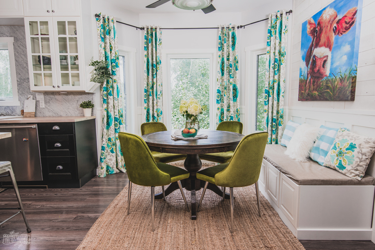 Colorful kitchen breakfast nook featuring a farmhouse table, turquoise drapes and velvet midcentury modern chairs