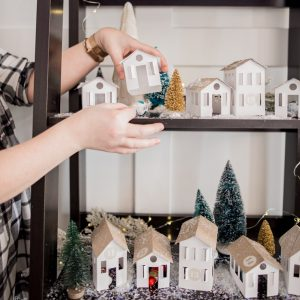 DIY Christmas Advent Calendar featuring handmade paper houses on a shelf