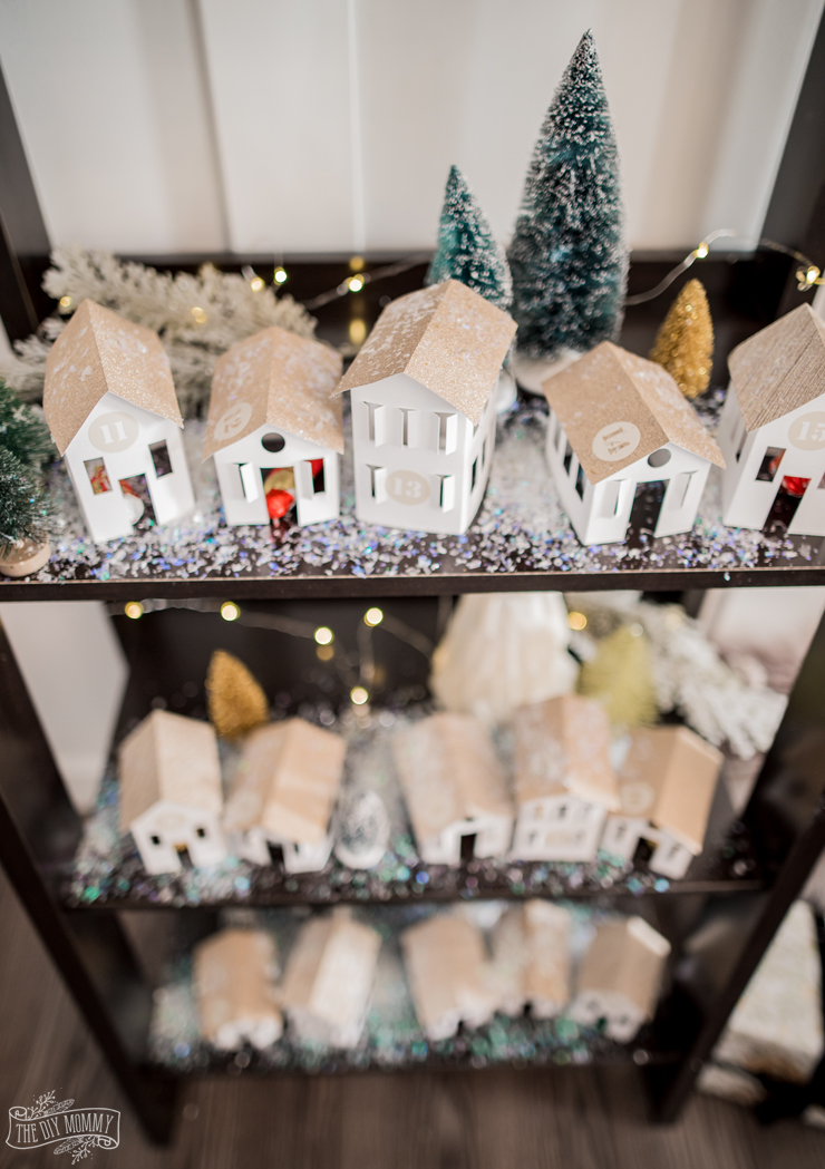 DIY Christmas Advent Calendar featuring handmade paper houses on a shelf