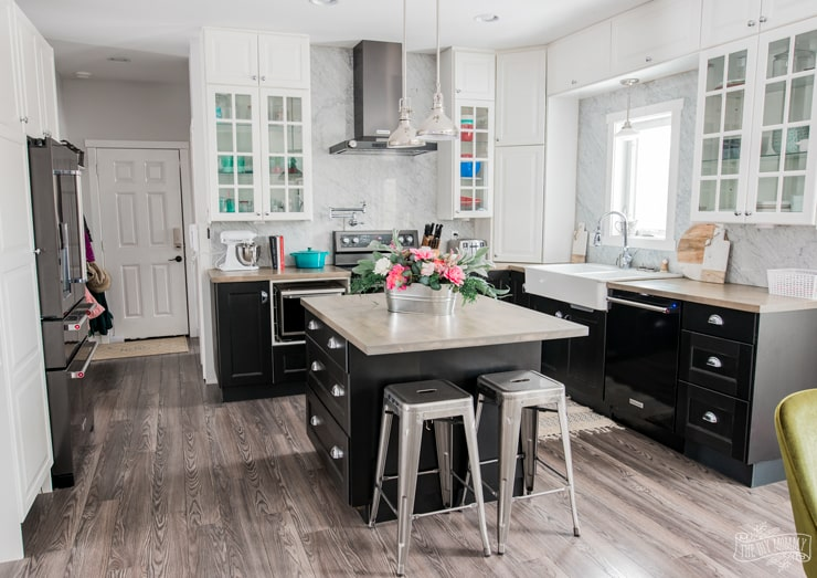 Black and white Ikea kitchen with stained and sealed butcher block countertops, black stainless steel appliances, dollar store floral arrangement