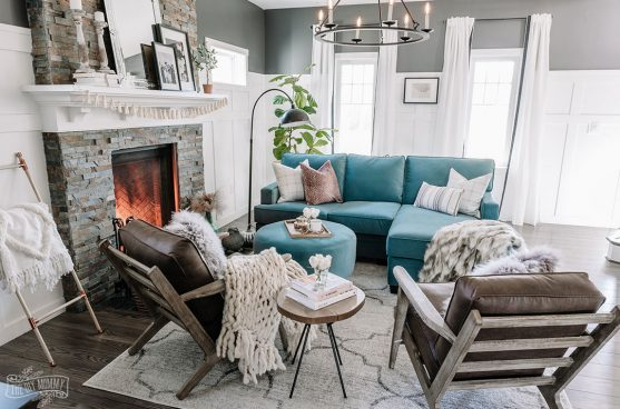 Eclectic living room with teal velvet sofa, brown leather chairs, and black and white walls