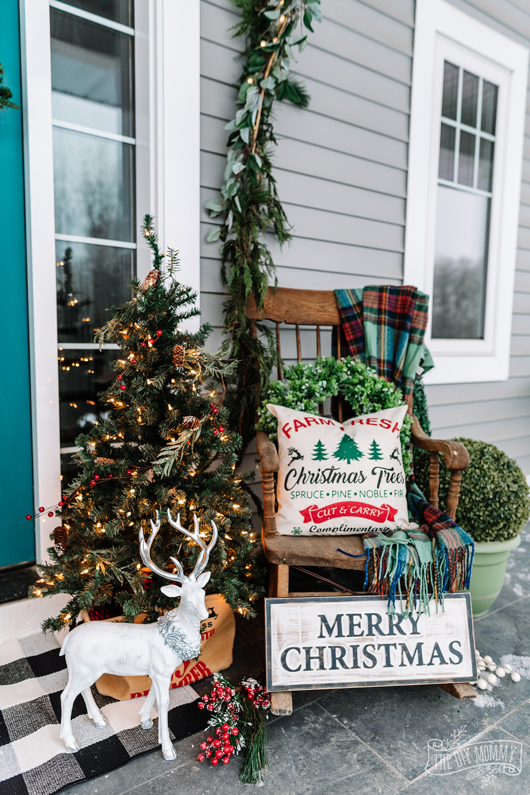 Christmas front porch in traditional farmhouse decor in reds, greens and teal colors