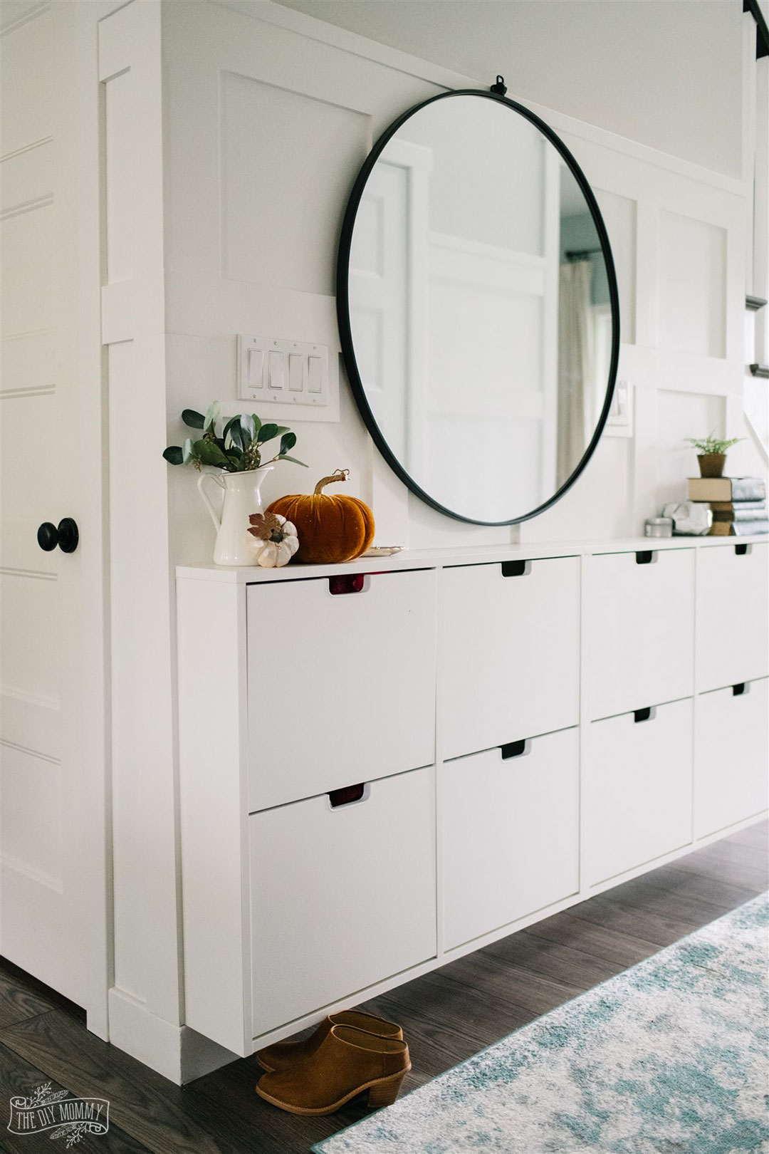 White entry with IKEA shoe cabinet hack and large round mirror decorated for Fall
