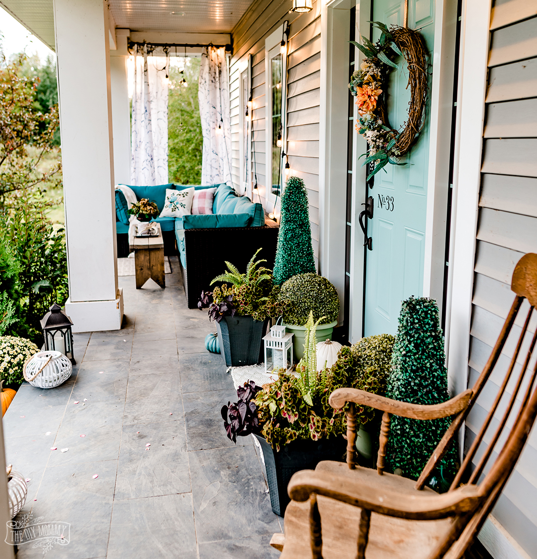 Beautiful Fall porch with pumpkins, mums, soft orange and aqua blue green.