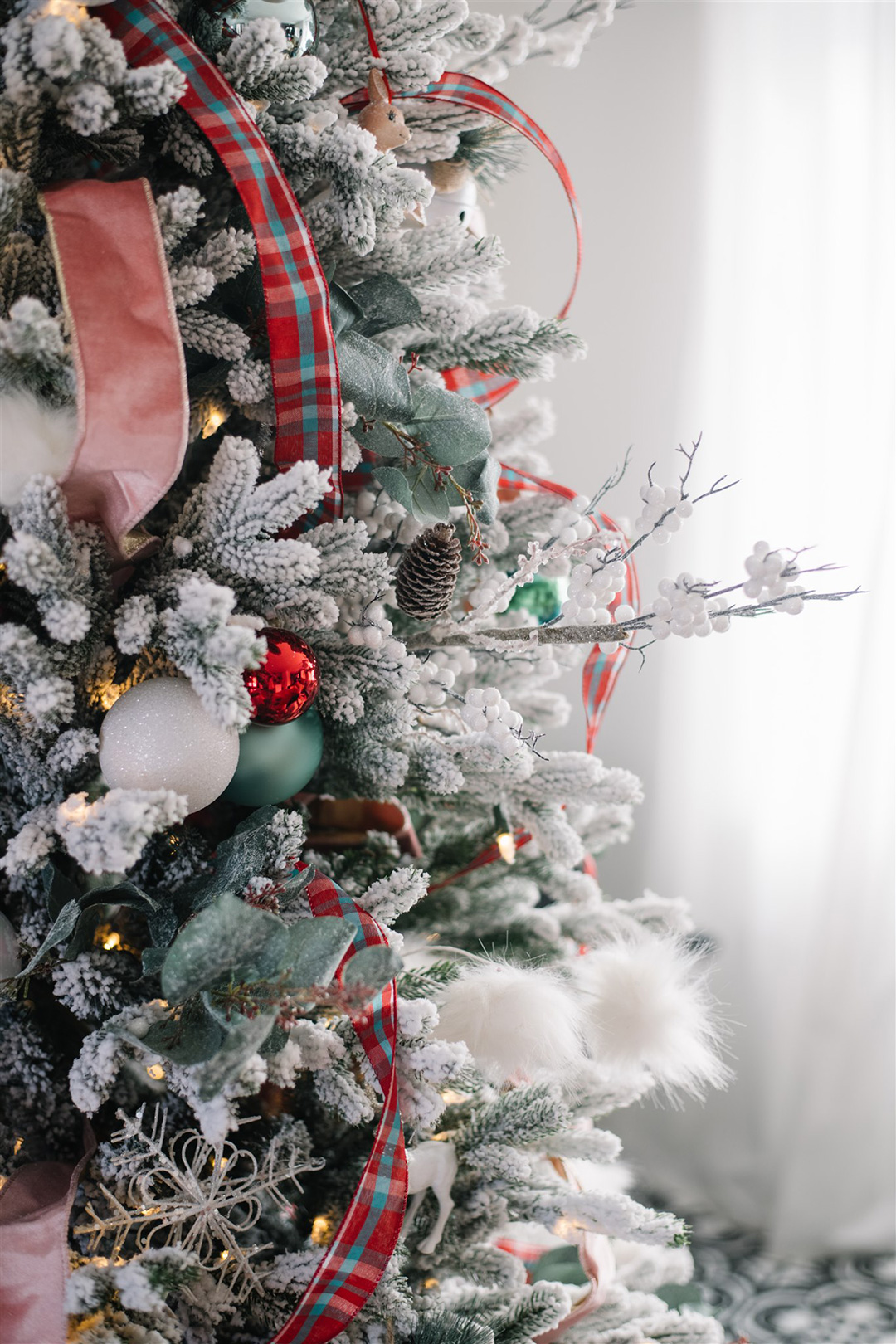 Christmas tree with turquoise and red plaid ribbon, flocked branches, pink velvet ribbon, and greenery picks