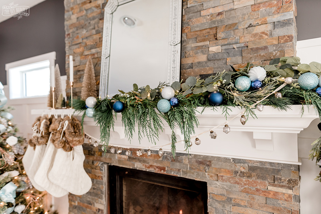 Christmas mantel with asymmetrical fresh greenery, blue colors, metallics, bottle brush trees and knit stockings.