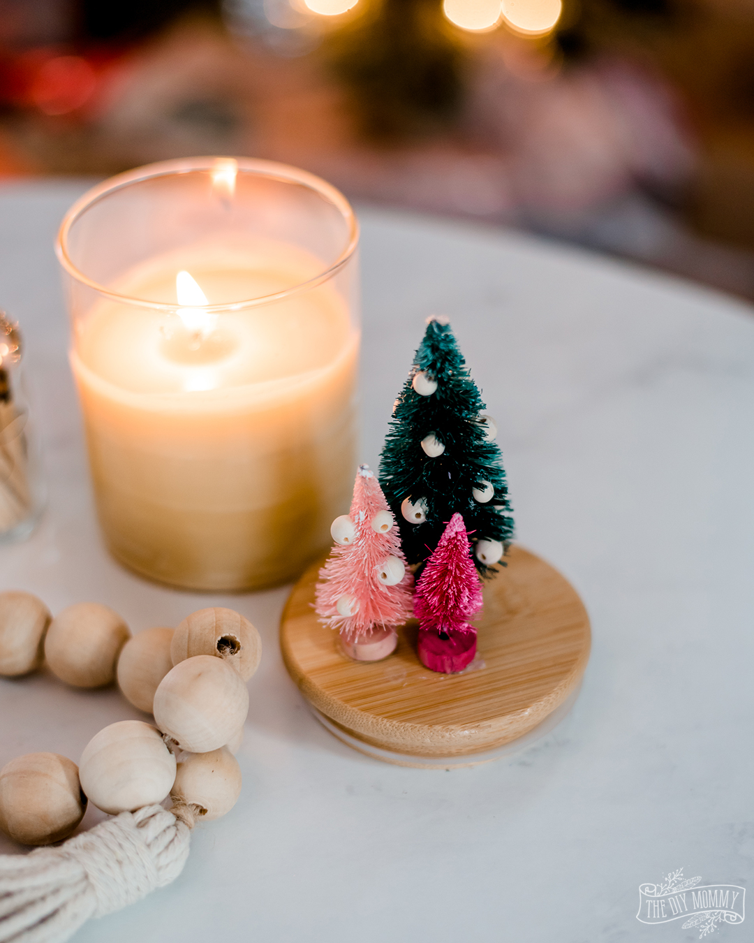 This is the cutest handmade gift! Make a DIY Christmas beeswax candle in a dollar store container and glue bottle brush trees to the lid.