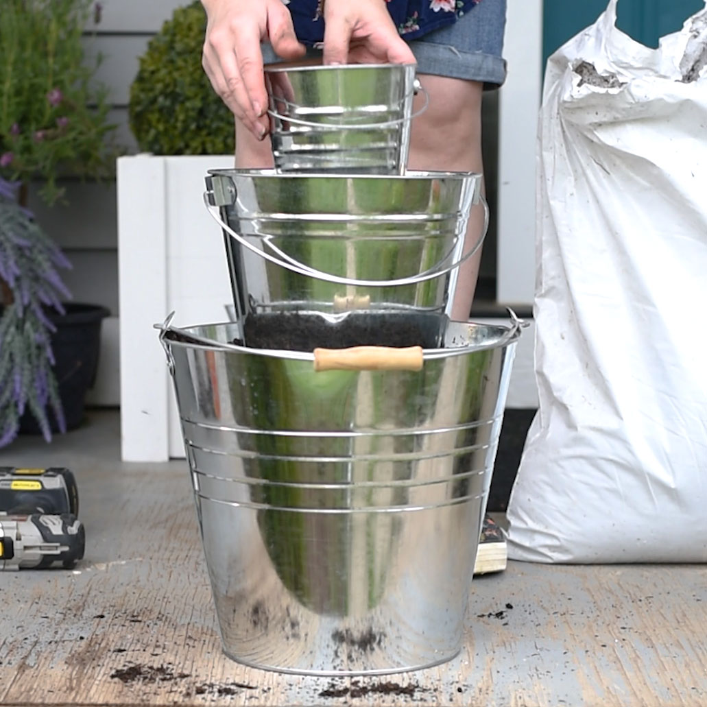 Make a beautiful DIY tiered herb planter from metal dollar store buckets. So easy!