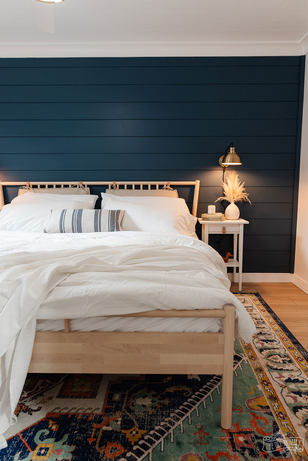 Modern coastal bedroom makeover with deep blue shiplap wall, vinyl plank flooring, IKEA furniture, and gold accents