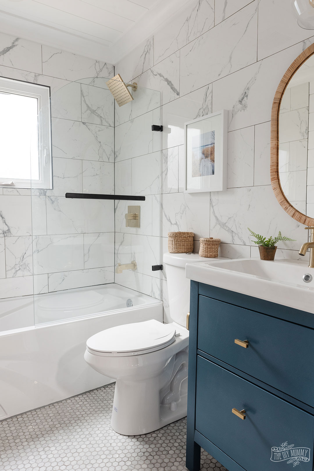 Modern coastal inspired bathroom renovation with marble tile, shiplap, gold and black accessories, clear shower door, blue and white colors & rattan accents