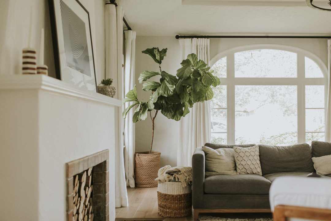 Transitional living room with dark gray couch, white walls, traditional light fixture and fireplace.