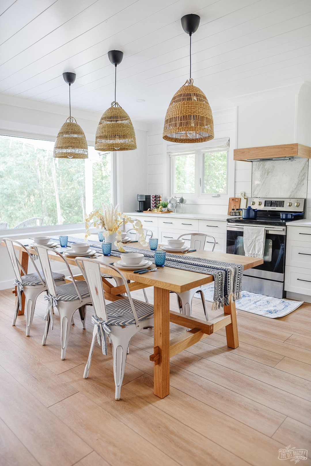 See how a dated honey oak kitchen was transformed into a coastal modern farmhouse kitchen with an eat-in layout, white shaker cabinets and white oak accents.