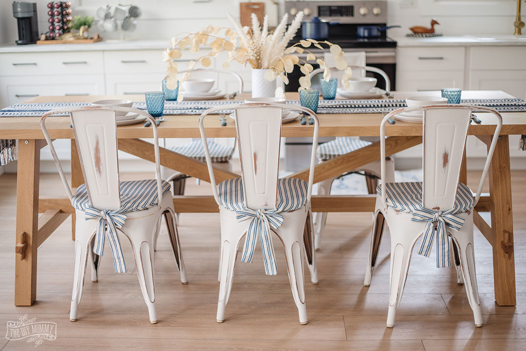 Need to make your metal farmhouse bistro chairs comfier? Learn how to sew these simple DIY chair pads with adorable bow ties at the back! These are an easy beginner's sewing project and you can make them to match any decor style.