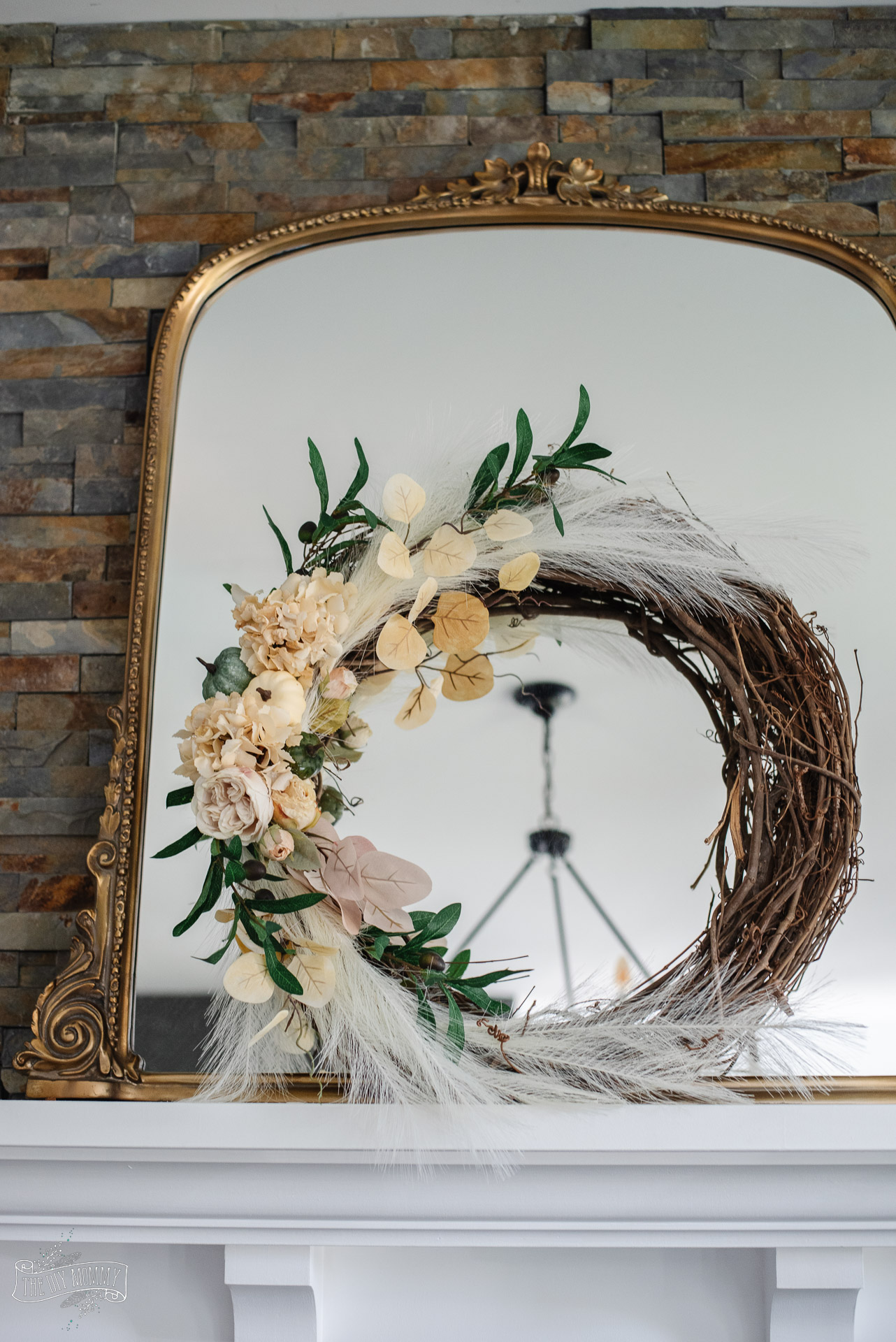Learn how to make a DIY Fall wreath featuring a grapevine base, muted Fall colors of cream and green, faux pampas grass, florals and olive branches.