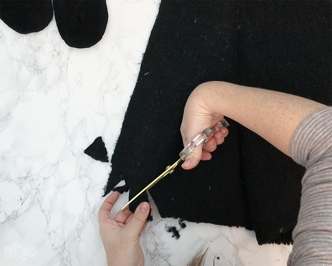 Cutting ear shapes from black scrap fabric