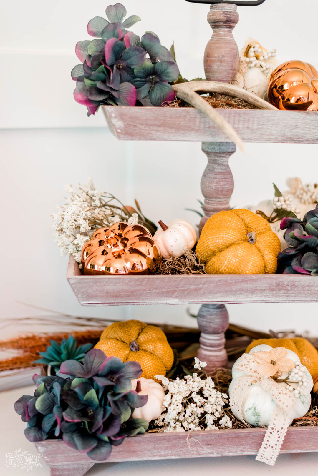 Learn how to make adorable boho chick pumpkins from dollar store pumpkins with chalk paint, a sanding sponge, hot glue, and faux florals.